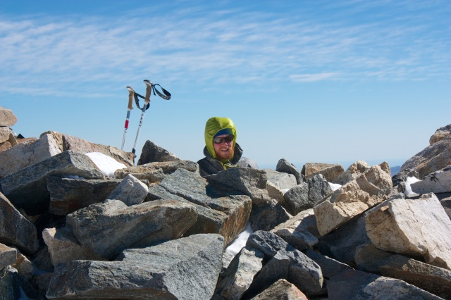 Junaid huddles behind some rocks to shelter from the wind while he sends out the SPOT from Gray's Peak.
